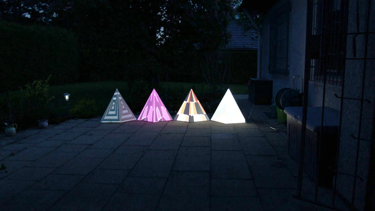 Tetrahedrons with colorful visuals projected on them in the garden.